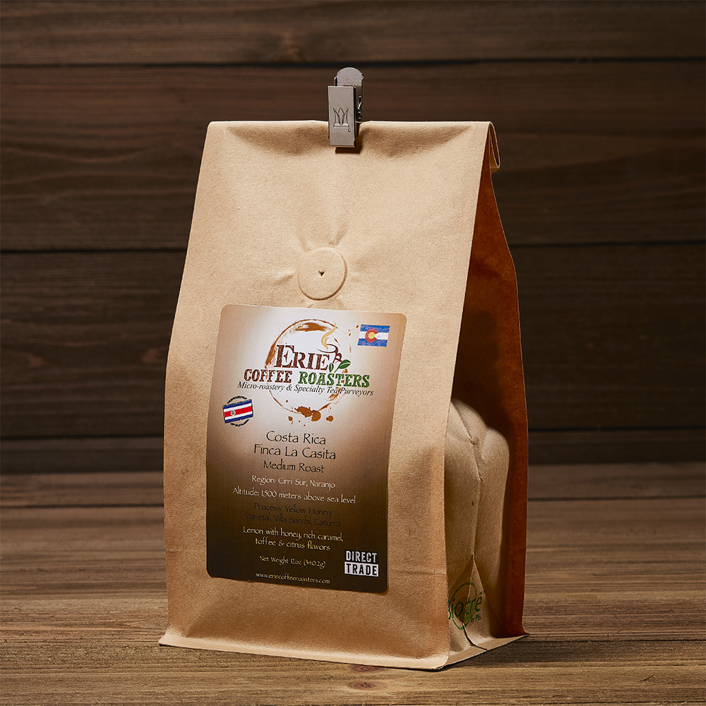 A paper coffee bag is photographed against a wood background.