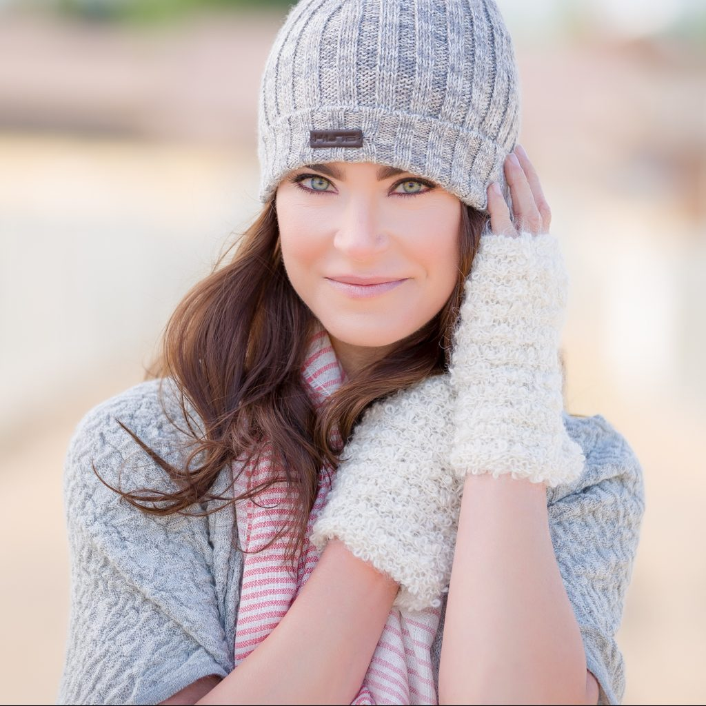 A brown-haired woman models alpaca fiber hat, scarf, and gloves